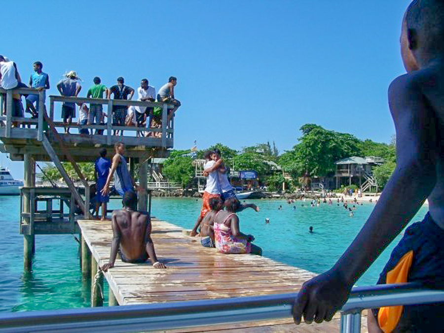 locals in West Bay playing and jumping off the pier in Roatan, Honduras