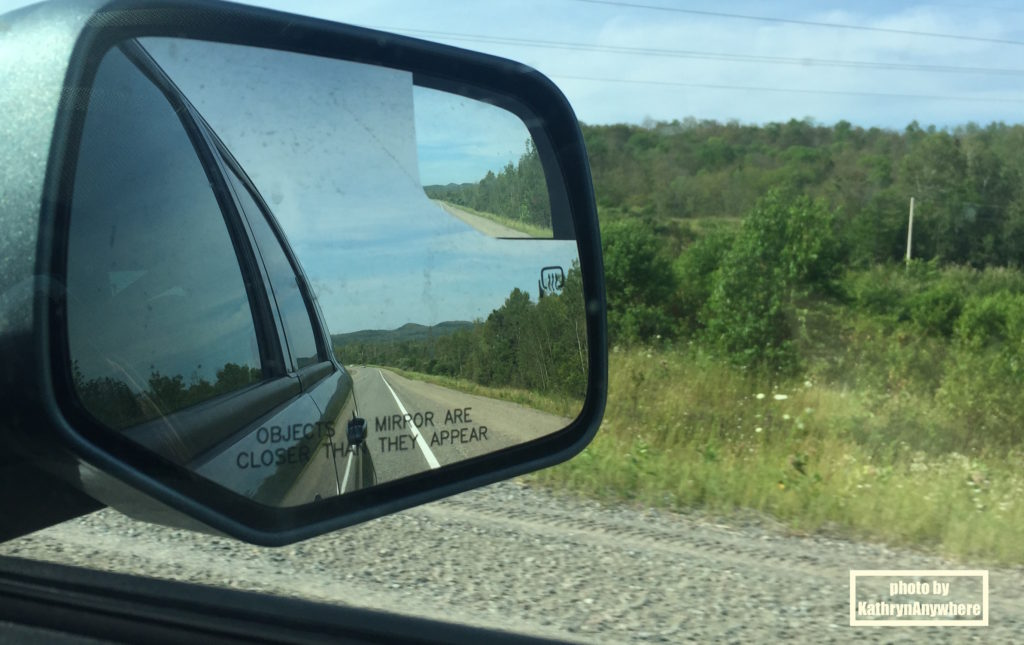 Ontario road trip - Rearview mirror of a vehicle with the road behind you.