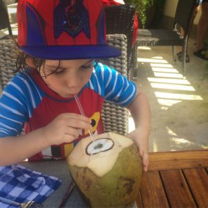 my son enjoying drinking from a coconut at Beaches Negril