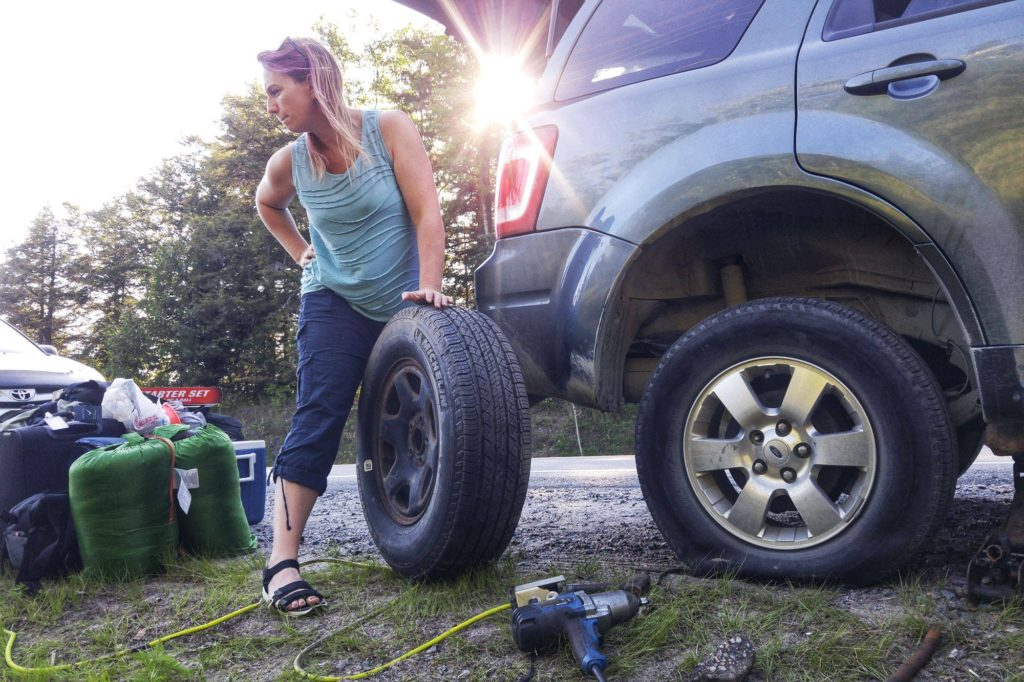 Woman with blown tire on the side of the road