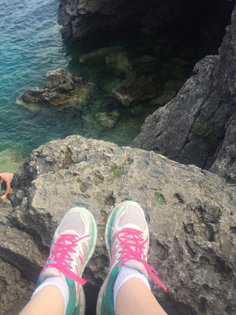 feet over ledge at grotto - Top 5 Things To Do In Tobermory, Ontario #topfivelist #tobermory #singingsandsbeach #provincialpark #brucepeninsula #flowerpotisland #thegrotto #brucepeninsulagrotto #parkscanada #smalltownsinontario #familytravelvlogger #familytravelblogger #ontariobloggers #ontarioroadtrips #thingstodoinontario #thingstodointobermory