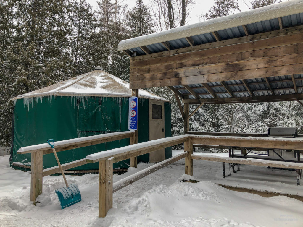 Green Ontario Parks yurt with accessible ramp for winter camping at MacGregor Point Provincial Park #findyourselfhere #macgregorpointprovincialpark #macgregorpoint #macgregorpp #ontarioparks #yurtcamping #wintercamping #outdoors #adventureparenting #portelgin #brucepeninsula