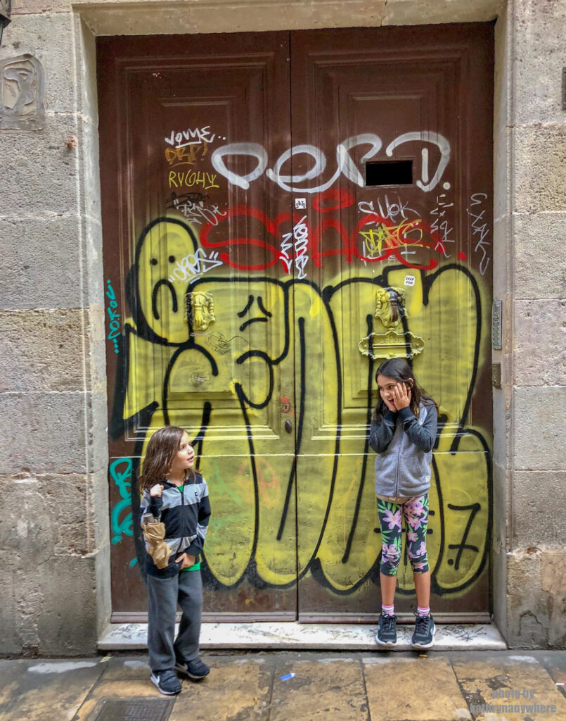 The doors of Lisbon, Barcelona and Paris. This graffiti decorated brown door my kids are posing in front of, was in one of the pedestrian alleys in the gothic quarter of Barcelona. My son had to pee and cut our walking trip short.