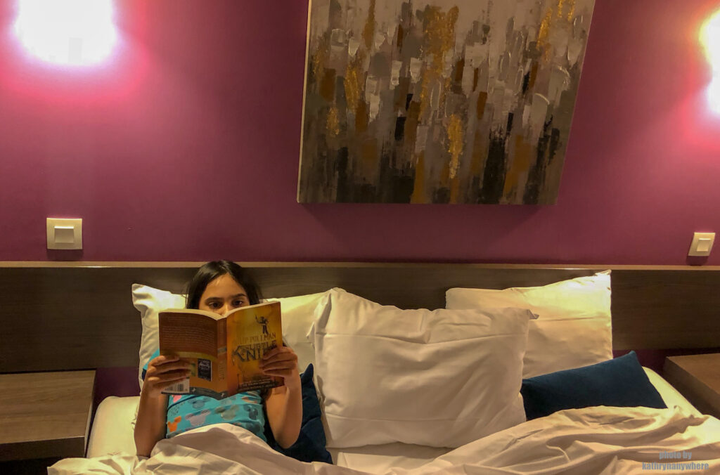 my daughter reading in the king size bed of our accommodations in Marseille, France