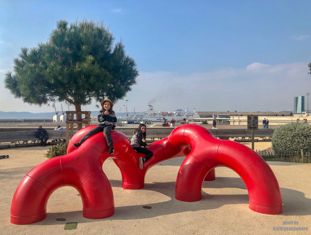 my children playing in a kid's playground in the old port area of Marseille, France