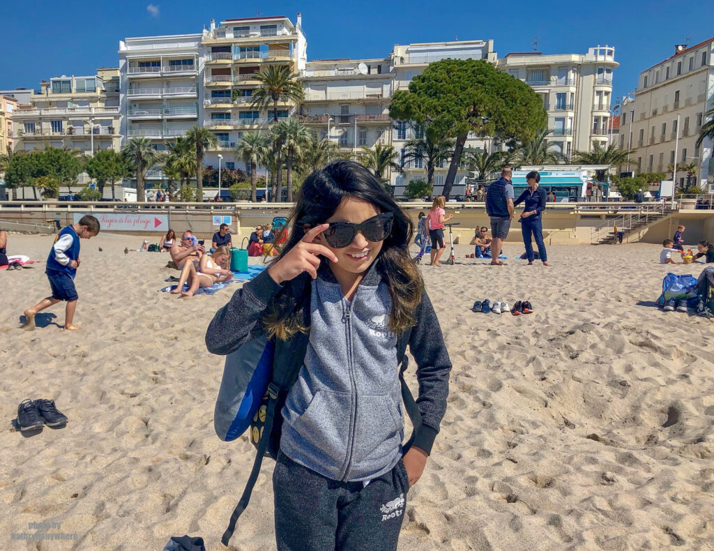 Glamour on the beach, wearing a Roots sweater in Cannes, France