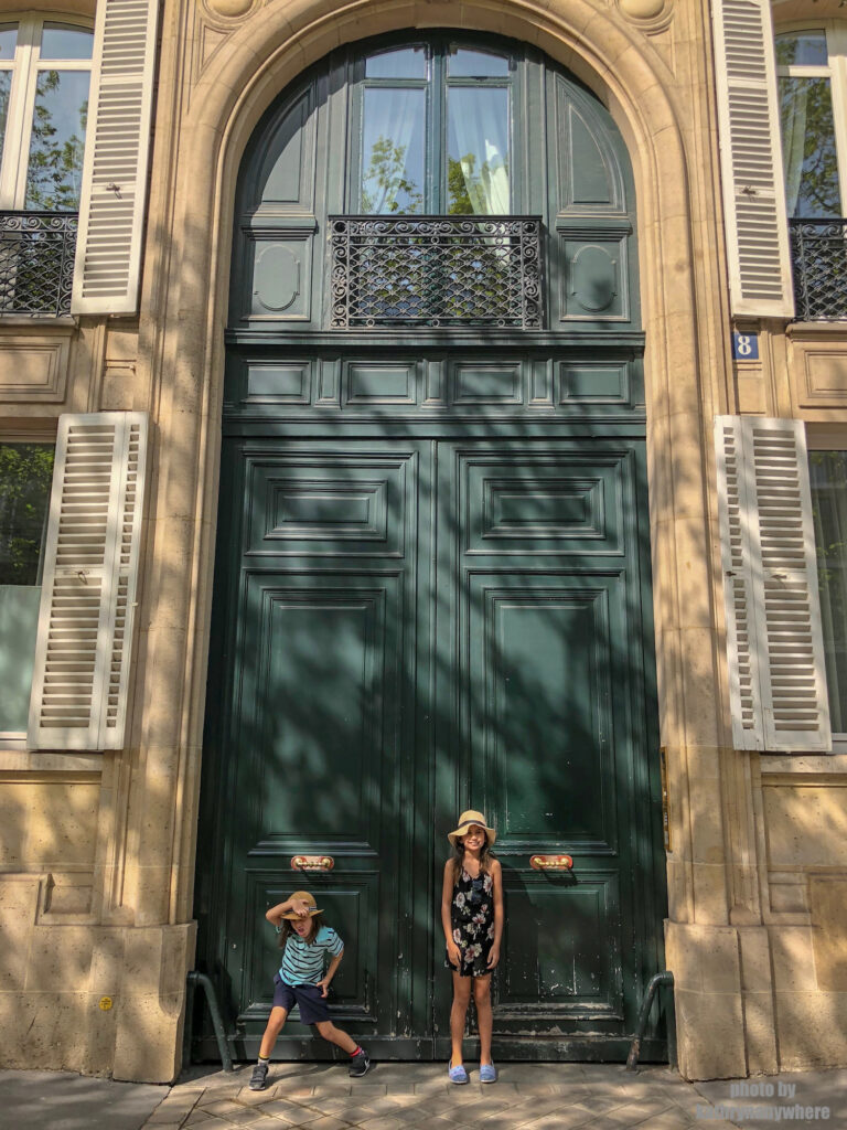 Really tall green door in Paris. This picture with my children was taken in 7th arrondissement neighbourhood in Paris, France