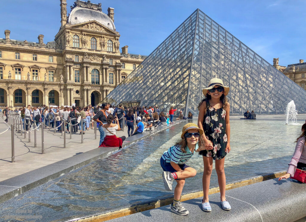Little Man and Miss M in front of the Lourve trying to avoid an instagram model... Paris, France