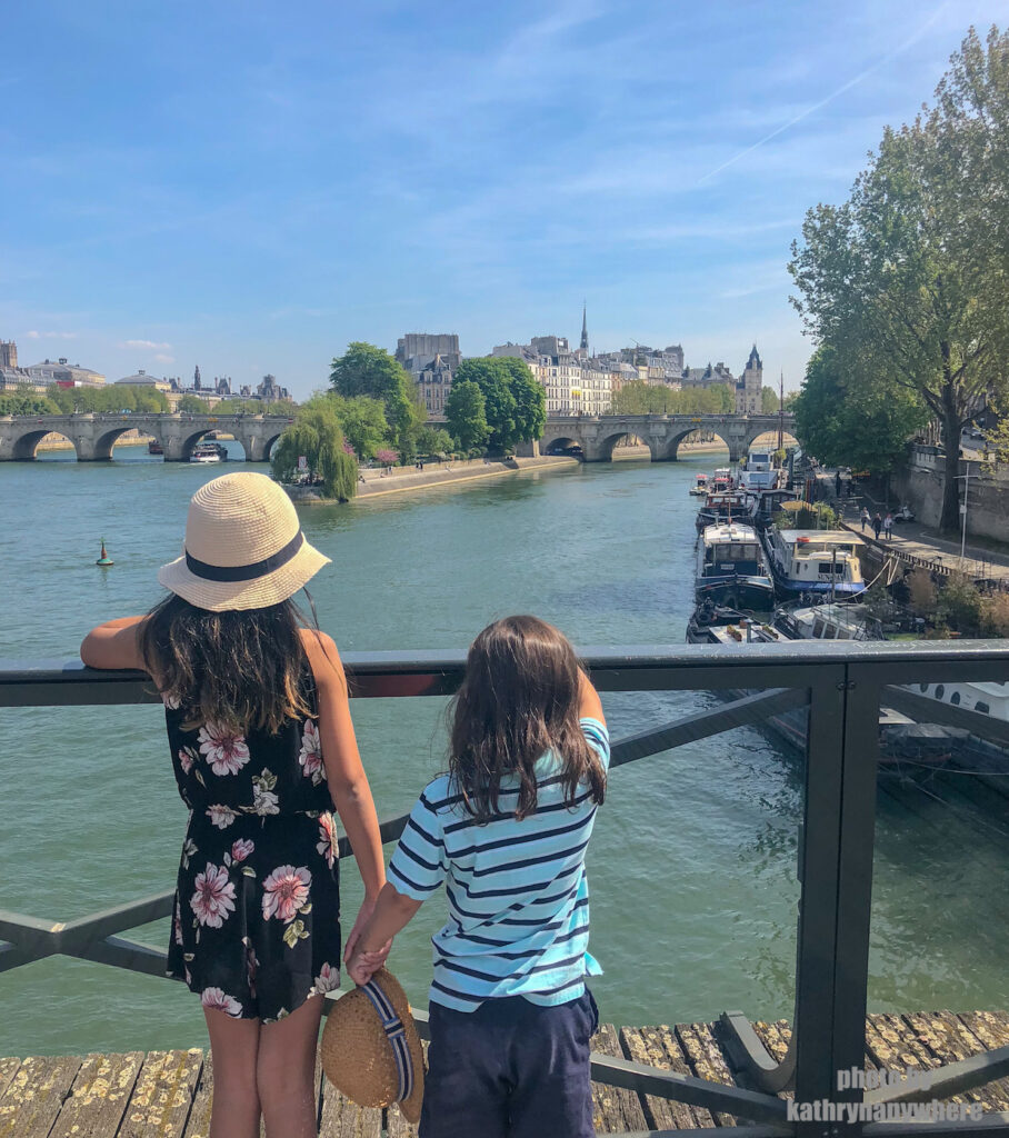 Miss M and Little Man looking at Notre Dam right after the fire on the bridge over the River Seine.