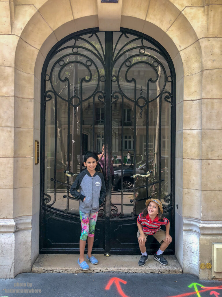 Short, glass door with black iron details in Paris. This picture with my children was taken in 7th arrondissement neighbourhood in Paris, France