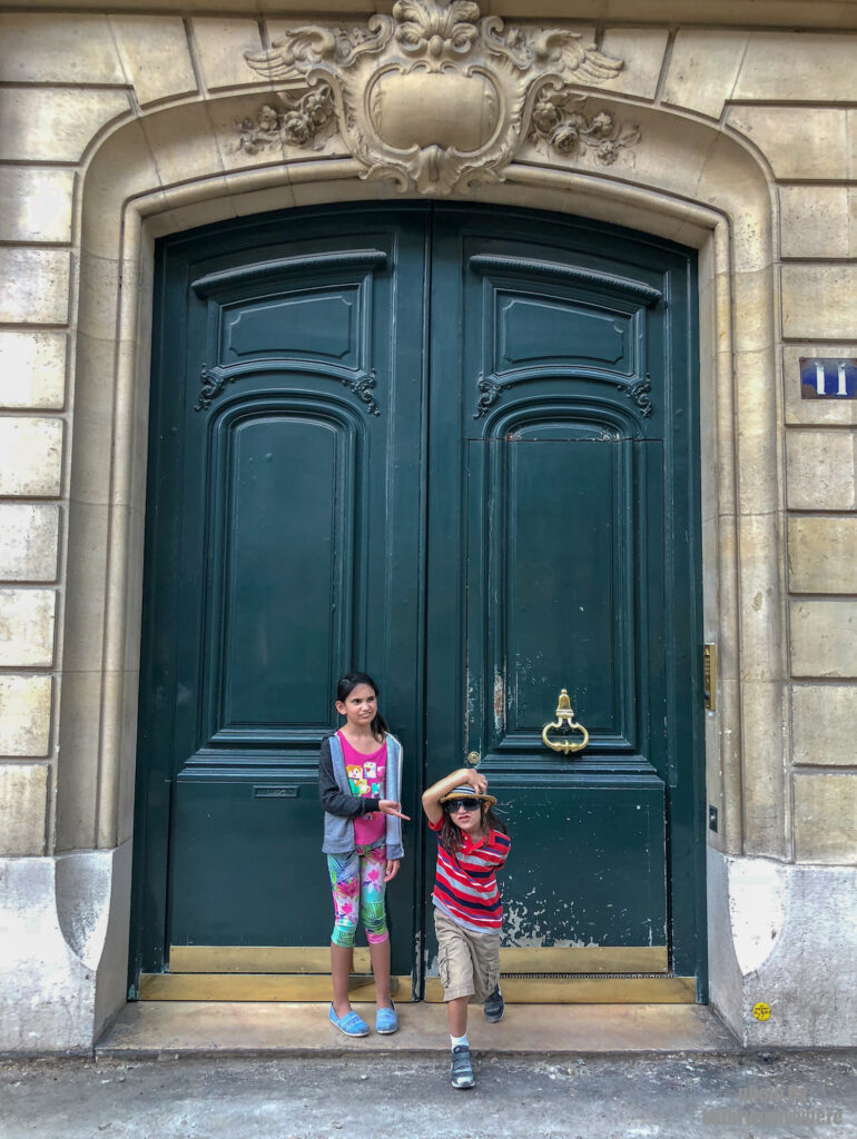 Short, green, wooden door without windows in Paris. This picture with my children was taken in 7th arrondissement neighbourhood in Paris, France