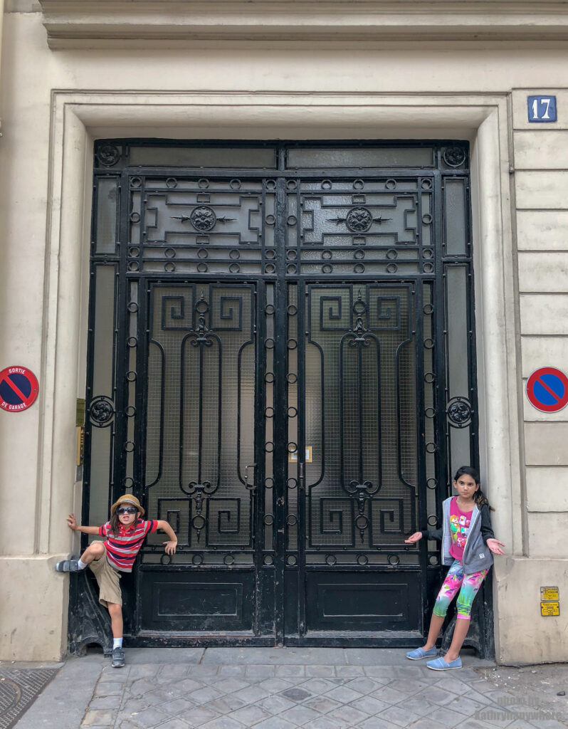 Glass door with iron design in Paris. This picture with my children was taken in 7th arrondissement neighbourhood in Paris, France