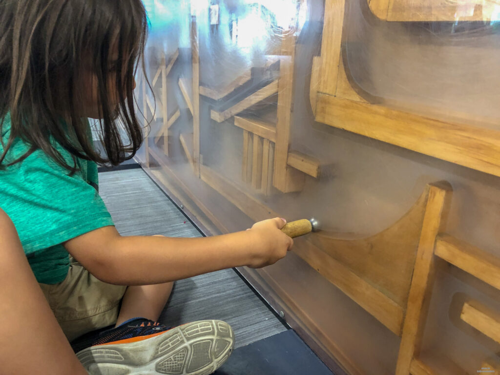 Little Man playing with a magnet and a metal ball in Discovery Space - a great place for kids to explore science and mechanics in State College, PA