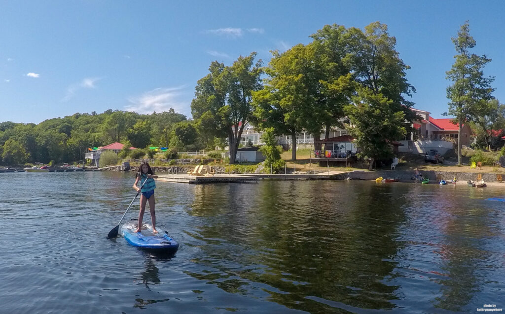 My daughter on a stand up paddleboard SUP on Stoney Lake in front of Viamede Resort