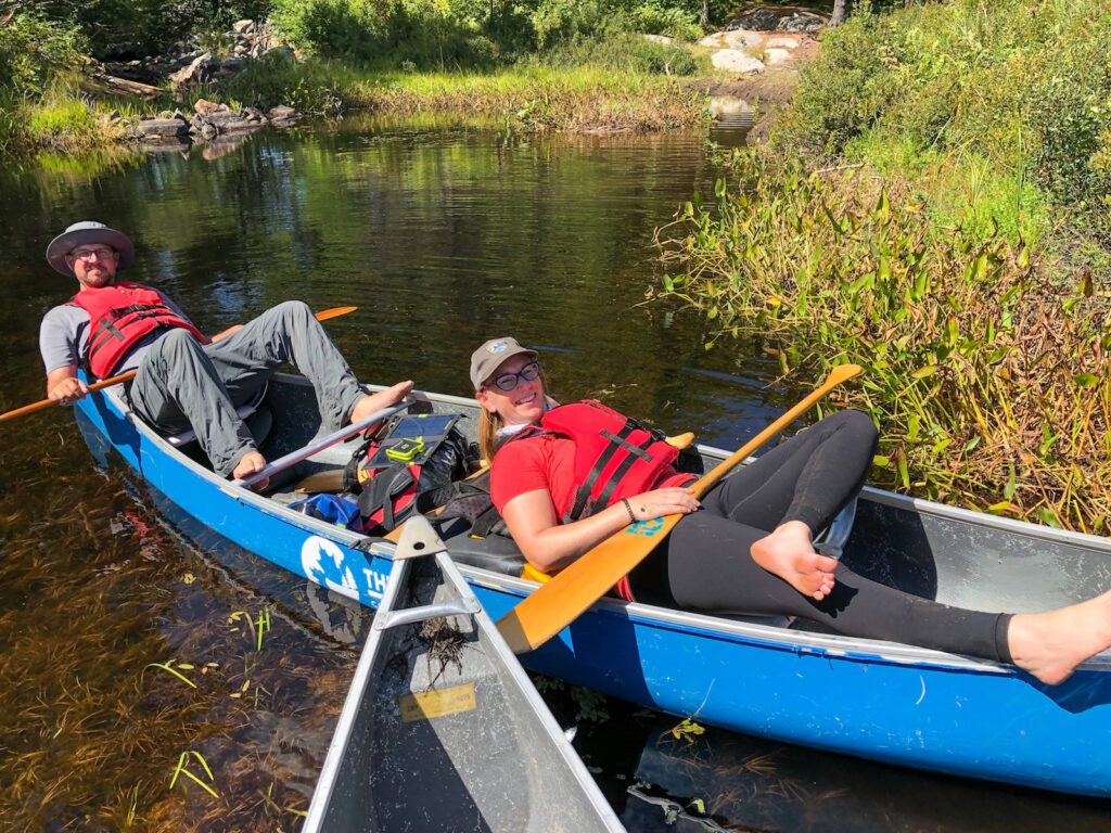Kevin from The Wandering Wagars and Kathryn from KathrynAnywhere relaxing during a canoe portage with friends in Kawartha highlands Provincial Park