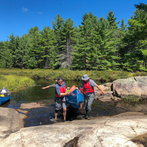 A couple men carrying a canoe over rocks in Kawartha Highlands provincial park