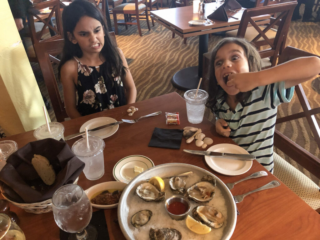 Little Man eating oysters at Traditions On The Beach at Island Inn, Sanibel Island