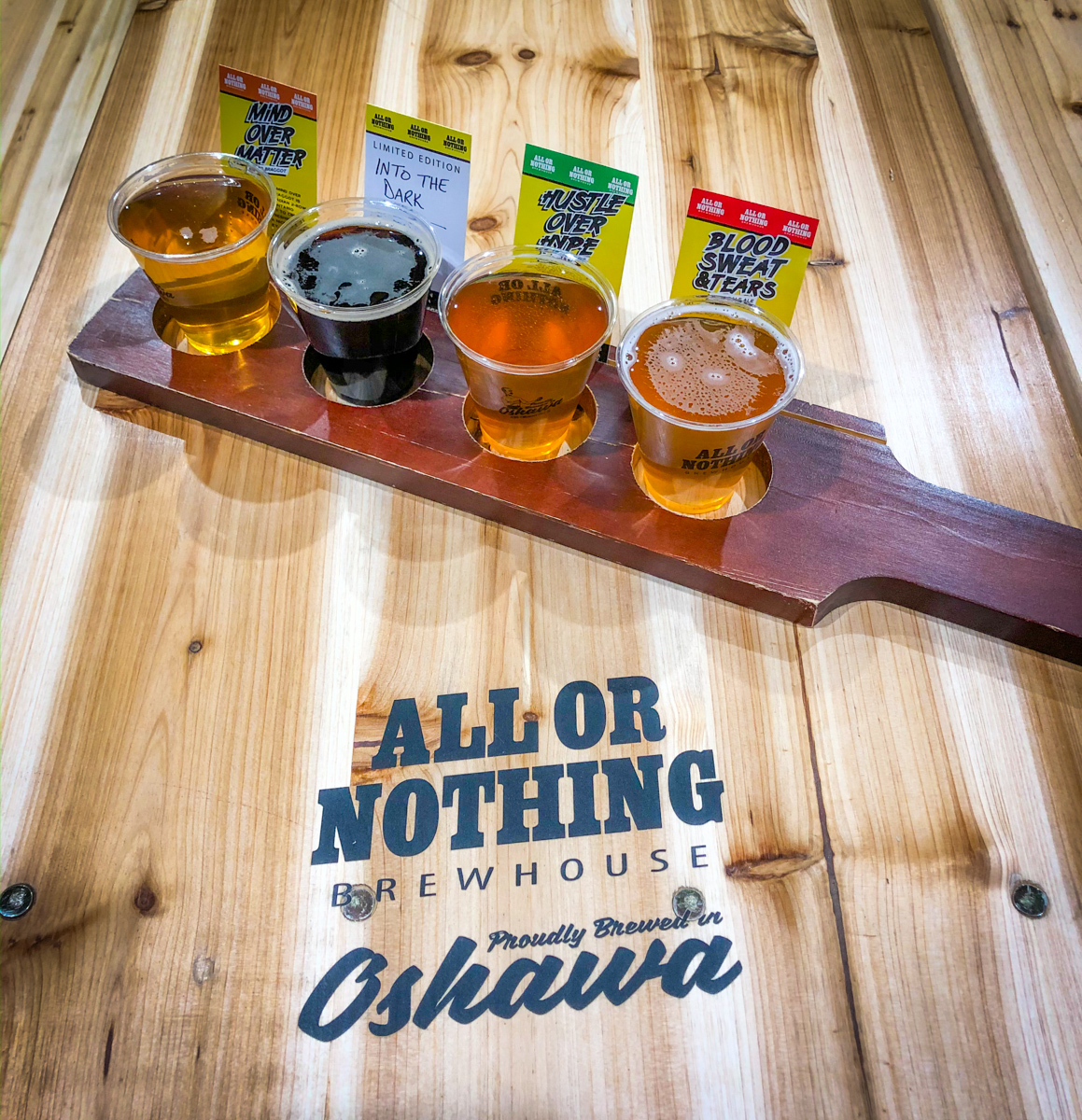 All or Nothing Brewhouse in Oshawa beer flight on wooden table with logo
