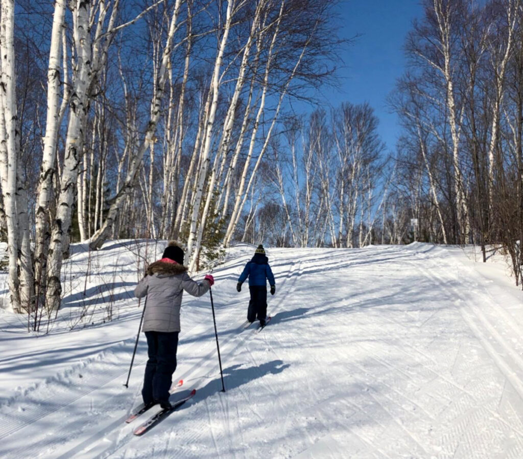 My kids heading up a small hill while cross country skiing in Kivi Park in Sudbury