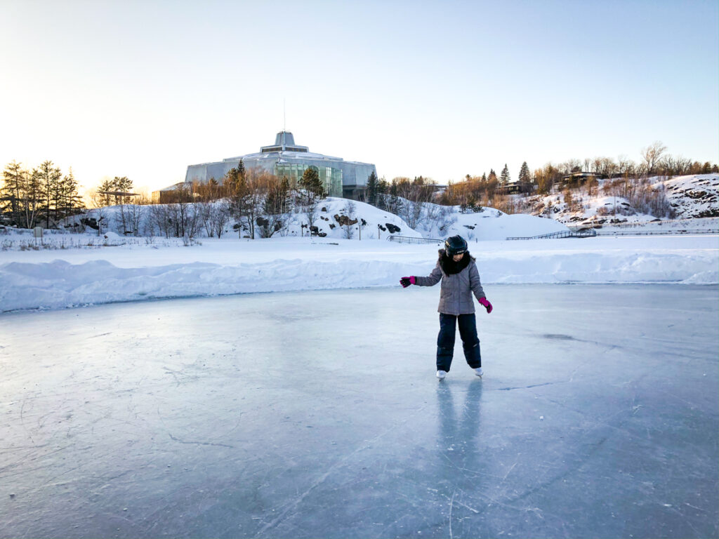 My daughter skating on Ramsey Lake with Science North in the background