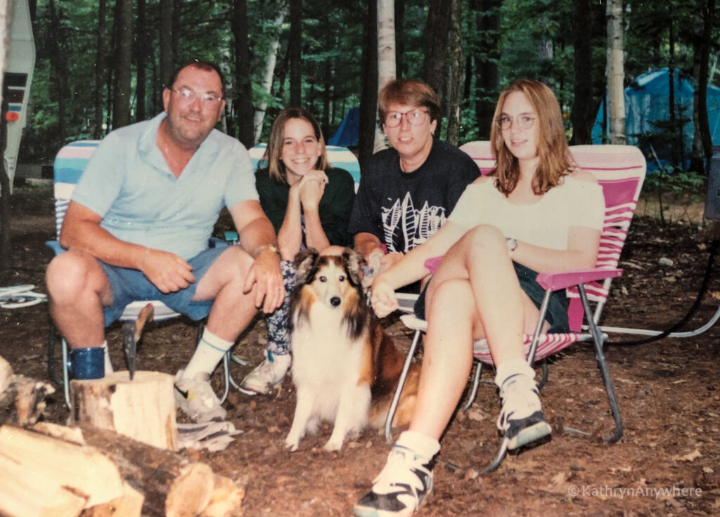 family at campfire with dog