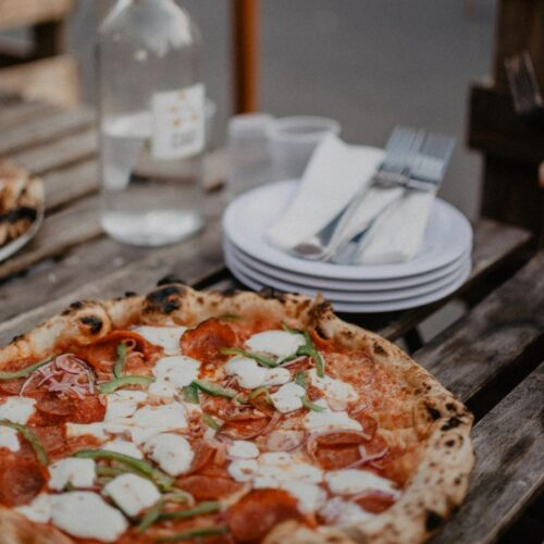 pizza with cheese on a plate on a patio, Restaurants On King Street West - Best Take Out Options in Toronto