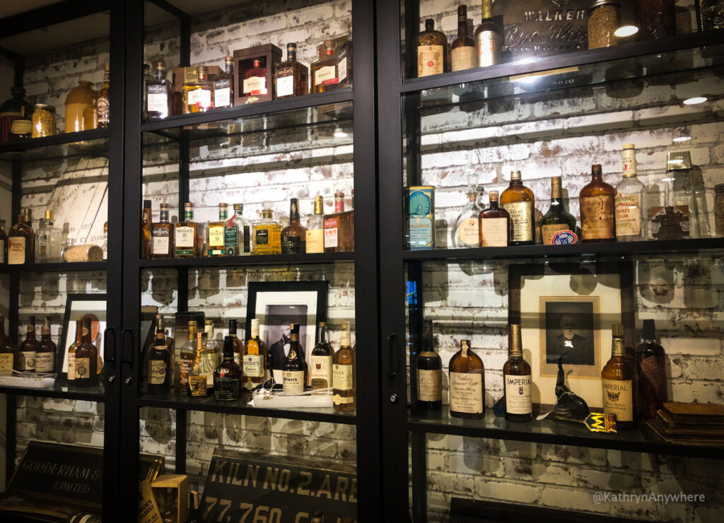 Selection of whisky bottles throughout history in J.P. Wiser's distillery bar in the shop. The Hiram Walker whisky tour starts here.