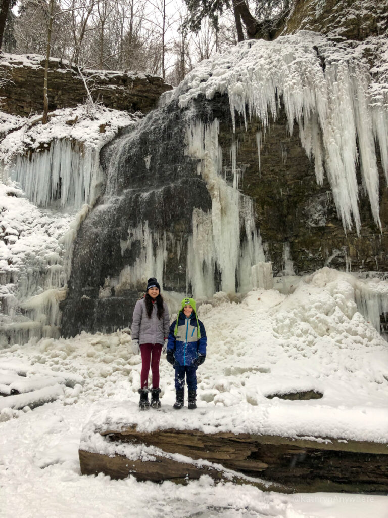 Tiffany Falls Ancaster Hamilton Ontario frozen in winter with two kids standing in front of it