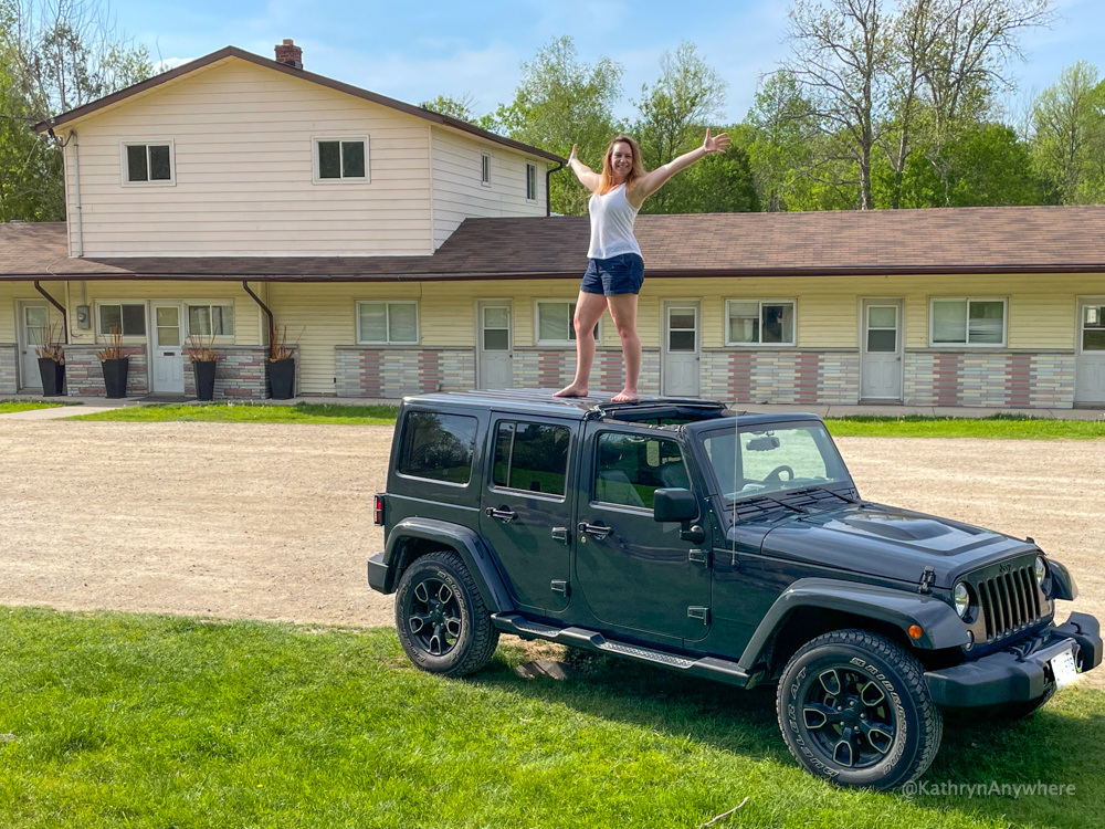 Kathryn Dickson standing on the roof of her Jeep In Front of Schitt's Creek Hotel Set
